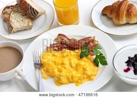 breakfast with scrambled eggs, crispy bacon, croissant,yogurt, orange juice and cafe au lait