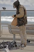 a homeless man wearing very dirty clothing shares his meal with the birds. poster