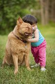 Outdoor summer scene of toddler giving hug to dog. poster