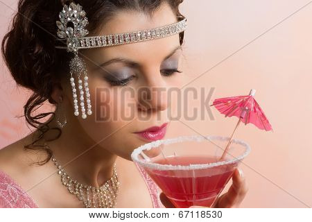 Beautiful young vintage 1920s woman with headband and flapper dress drinking a cocktail