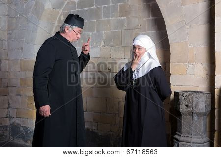 Priest giving a young novice a reprimand