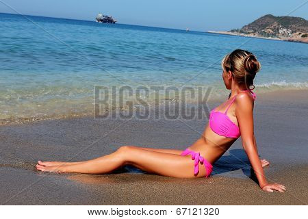 Side View Of Young Woman Sitting On The Beach