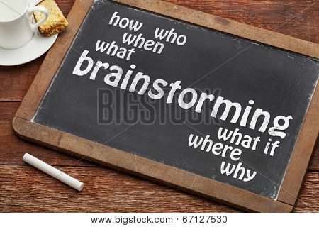 brainstorming word with who, what, when, where, how questions on a vintage slate blackboard with a cup of coffee