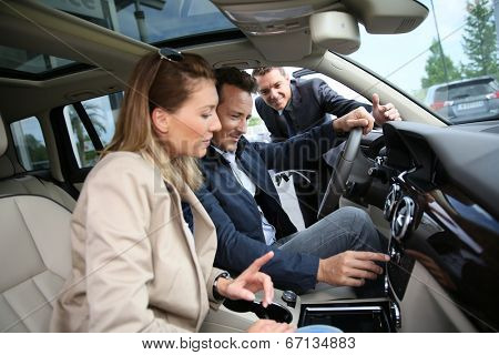 Car dealer showing vehicle binnacle to clients