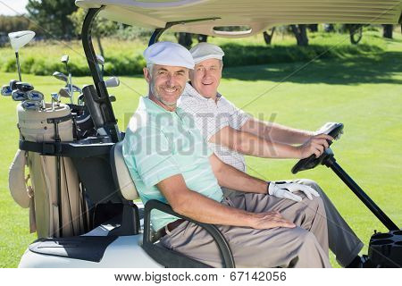 Golfing friends smiling at camera in their golf buggy on a sunny day at the golf course
