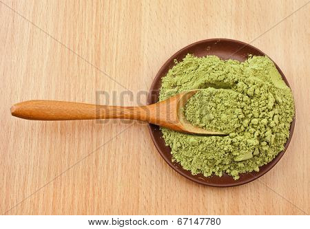 Powdered Green Tea Matcha in spoon on wood table surface  background