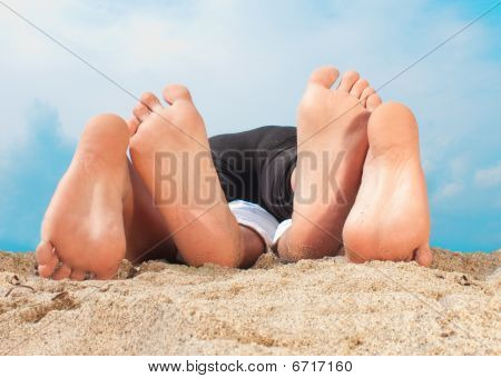 Couple Playing On The Sand With Feets
