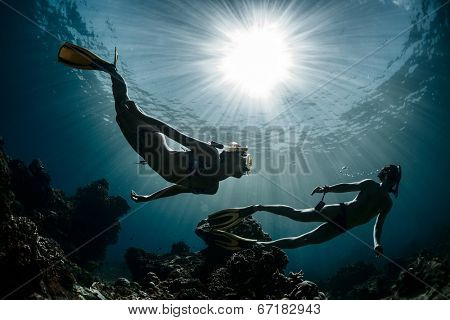 Underwater shot of the couple moving on depth over coral reef