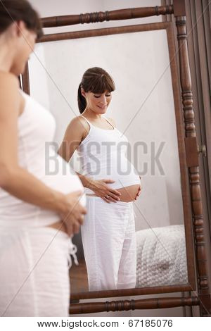 Pregnant woman looking in mirror
