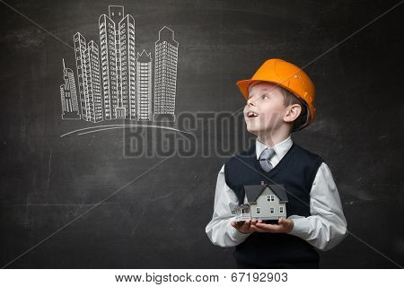 Portrait of boy in hard hat keeping home model and looking at chalky drawing of buildings on grey background