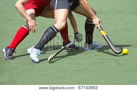 Close up of two field hockey players, challenging eachother for the control and posession of the ball during an intense, competitive match on professional level