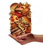 Over eating and compulsive indulgence of fast food concept as a hand holding up a huge stack of junk food as hamburgers hotdogs and french fries as an unhealthy diet nd bad nutrition symbol isolated on a white background. poster