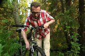 Tourist repearing his old bike in the woods poster