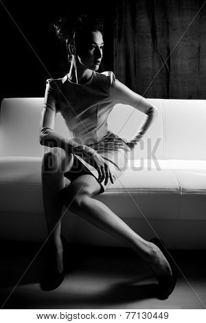 Black And White Portrait Of Fashion Female Model Sitting On White Couch