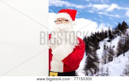 christmas, holidays, advertisement and people concept - man in costume of santa claus with white blank billboard making hust gesture over snowy mountains
