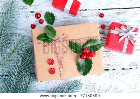 Beautiful Cristmas gifts with European Holly (Ilex aquifolium) on wooden background