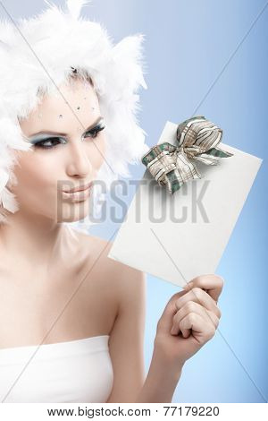 Beautiful woman in luxurious winter makeup and feather cap holding christmas present, looking at it curiously.
