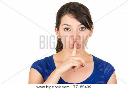 beautiful young woman gesturing silence shhh with finger on mouth