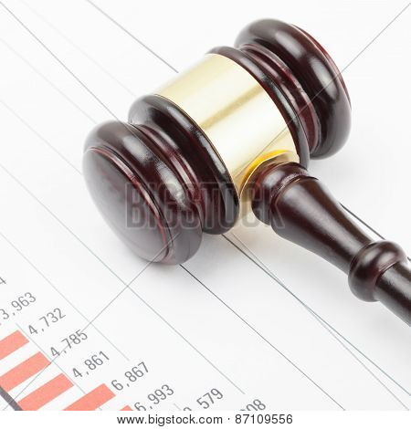 Wooden Judge's Gavel Over Colorful Chart