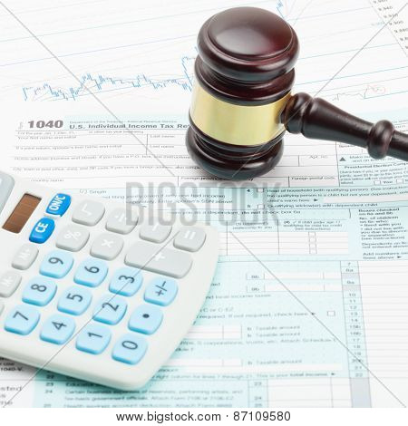 Wooden Judge's Gavel And Calculator Over Us 1040 Tax Form