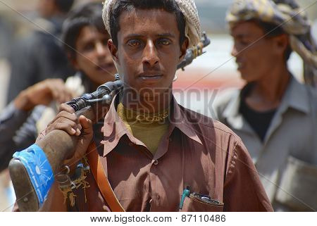 Young Yemeni man holds a rifle in Aden, Yemen.