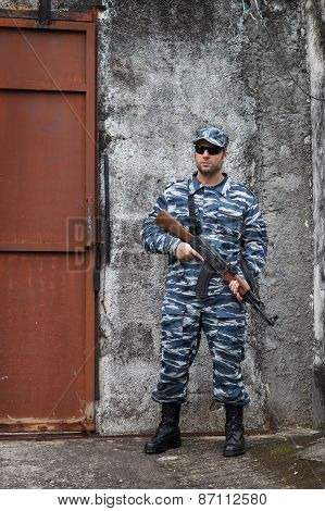 Caucasian Military Man With Black Sunglasses In Urban Warfare Holding Grifle Near Iron Door
