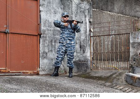 Caucasian Military Man In Urban Warfare Protecting Iron Gate With Grifle