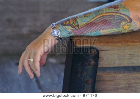 Tattooed arm w/watch and ring.