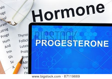 Papers with hormones list and tablet  with word progesterone.