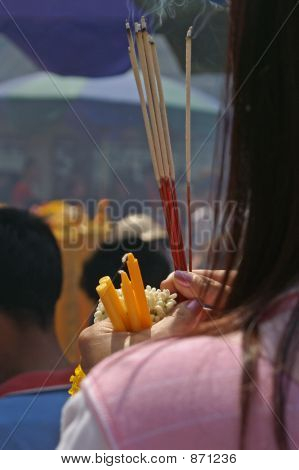 Closeup of lady holding incense and candles at shrine in Bangkok,Thailand