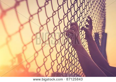 Hand holding on chain link fence Vintage filter effect poster