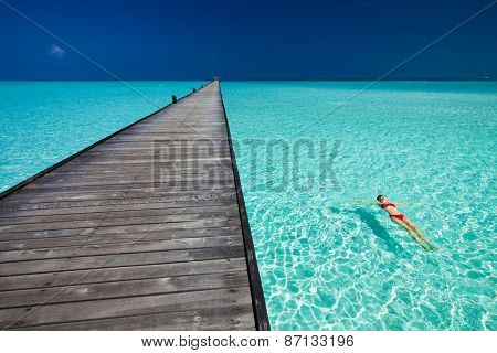Young woman in red bikini swimming next to jetty in azure water of Maldives