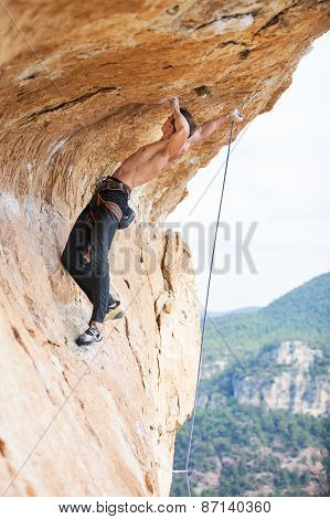 Young man clipping rope while clinging to cliff