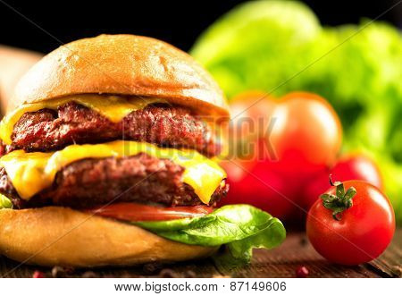 Hamburger with fries on wooden table. Cheeseburger on fresh buns with succulent beef patties and fresh salad ingredients served with French Fries on crumpled brown paper on a rustic wood table poster