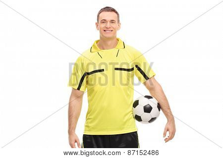 Male football referee in a yellow jersey holding a ball and looking at camera isolated on white background