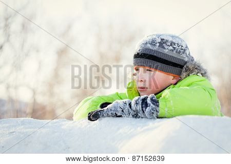 Happy Child In Winterwear Smiling While Playing In Snowdrift