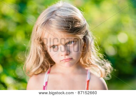 Close-up Portrait Of Capricious Blond Little Girl With Pursed Lips
