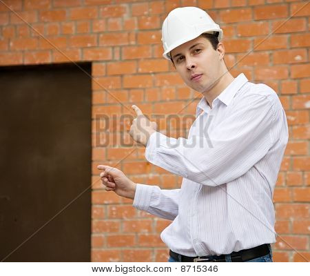 Builder Pointing To Door In Brick Wall