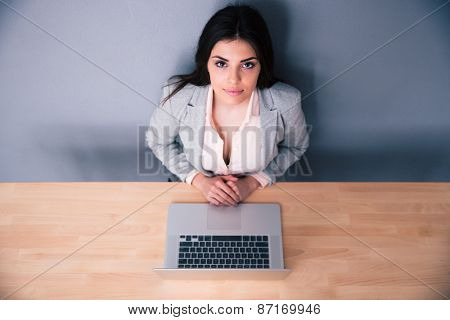 Yuong businesswoman sitting at the table with latpop over gray background. Looking at camera