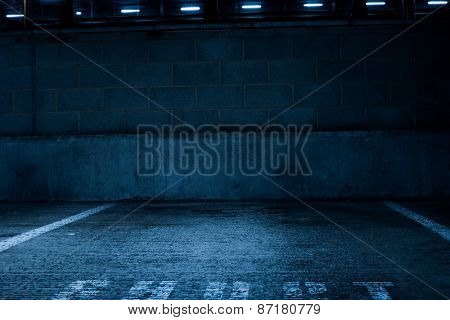 Simple Architectural Design of an Empty Rustic Concrete Car Park with Low Light Inside the Building