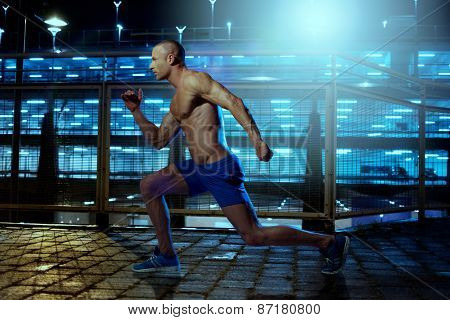 Handsome Young Athletic Guy with No Shirt Exercising Inside a Building Wile Facing to the Left of the Frame.
