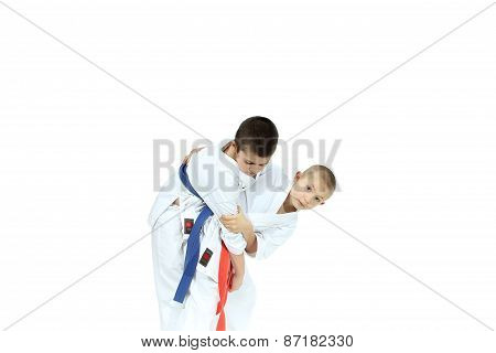An athlete with a red belt is doing throw Judo