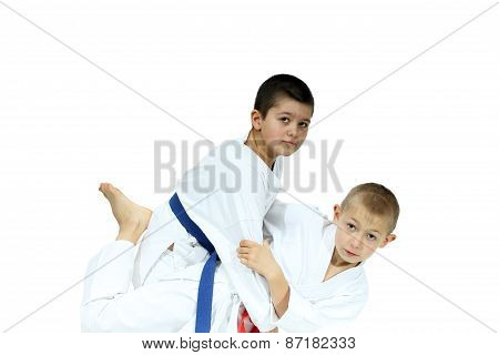 An athlete with a red belt performs grip for throw poster