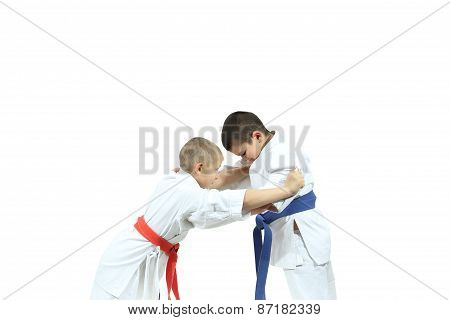 Boy with red belt are perfoming capture judogi the sportsman with blue belt poster