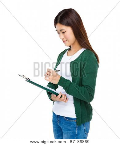 Young girl take note on check list board