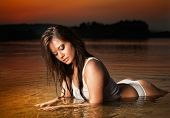 Sexy brunette woman in lingerie laying in river water. Young female relaxing on the beach during sunset. Perfect body girl with wet clothes and hair posing provocatively in summer evening at beach poster
