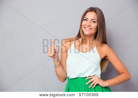Portrait of a casual pretty woman showing thumb up over gray background and looking at camera