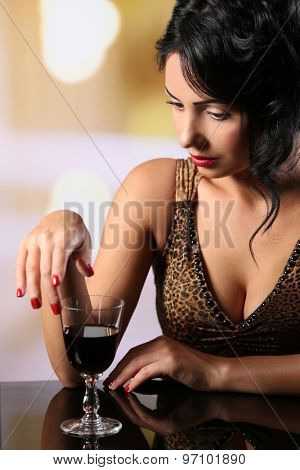 Pretty young brunet with wineglass on light blurred background poster