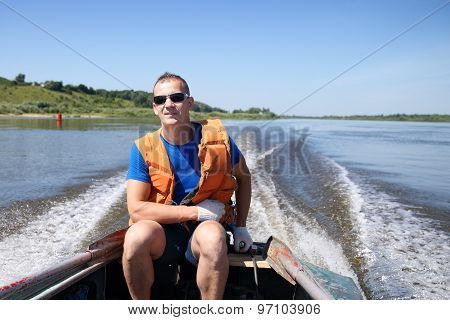 man in  life jacket on boat is moving quickly