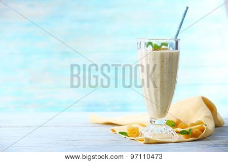Glass of raspberry smoothie on wooden table on turquoise background